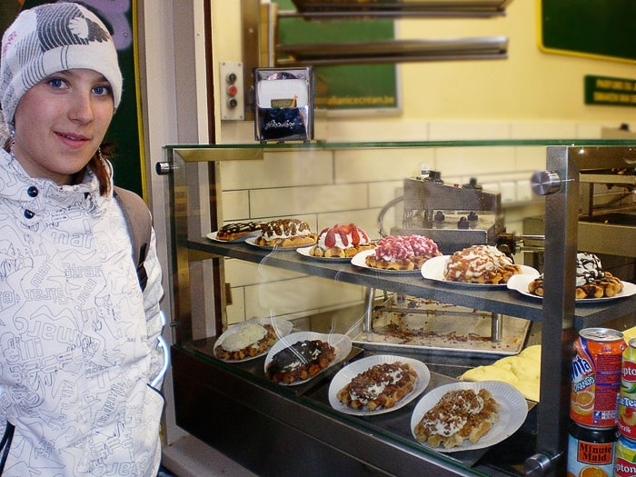 ženska stoji pred prodajalno belgijskih vafljev