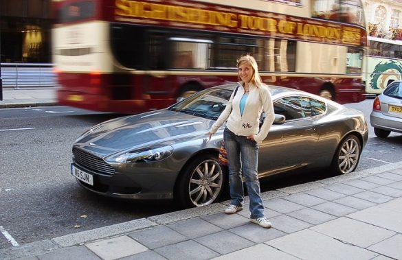 ženska stoji ob avtomobilu Austin Martin
