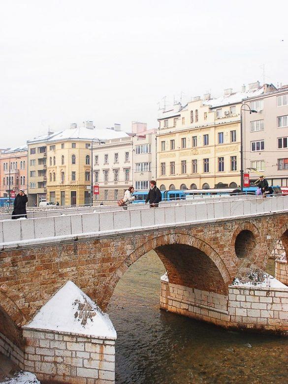 moški in ženska na mostu v Sarajevu