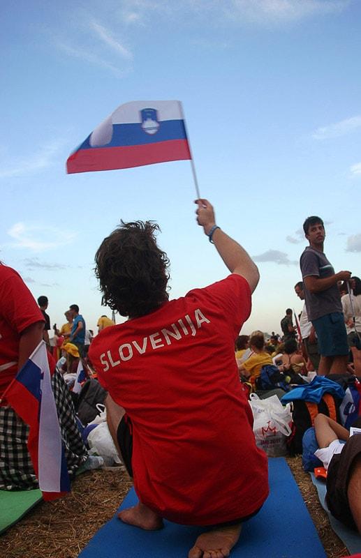moški v rdeči majici z napisom Slovenija in s slovensko zastavo v rokah