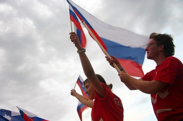 moški in ženska s slovensko zastavo v rokah