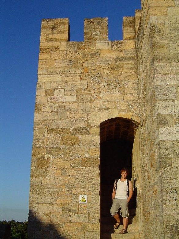 moški pred oglatim obrabnim stolpom lizbonskega gradu Sao Jorge