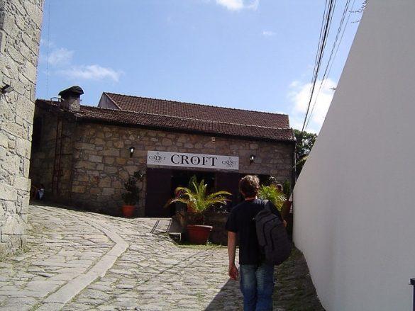 moški hodi po tlakovani ulici proti vinski kleti Croft, Porto