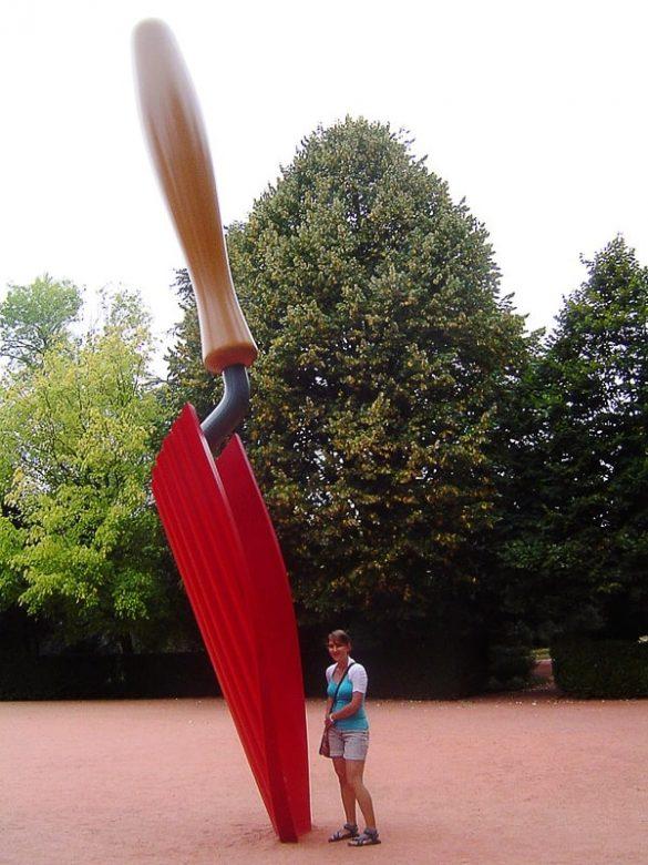 ženska stoji ob gigantski lopati
