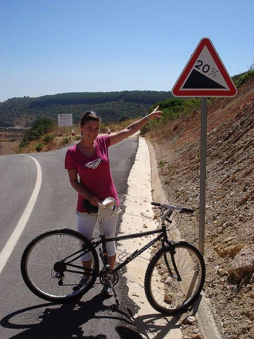 ženska na kolesu ob znaku, ki opozarja na 20% klanec