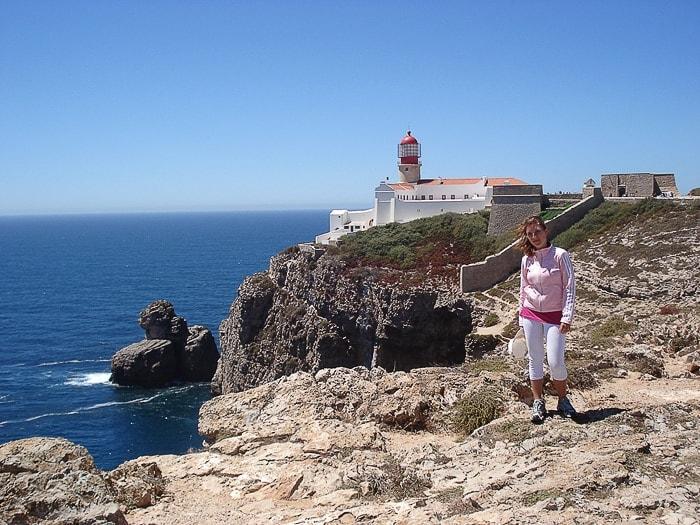ženska stoji na pečini pred svetilnikom na rtu Cabo de São Vicente