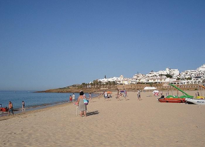 turisti na peščeni plaži, v ozadju belo obmorsko mesto Luz
