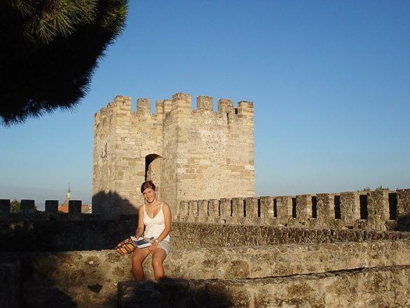 ženska sedi na obzidju gradu Sao Jorge, Lizbona