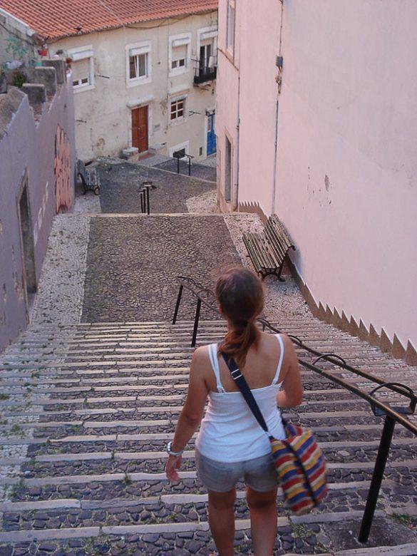 ženska s pisano torbico hodi po stopnicah