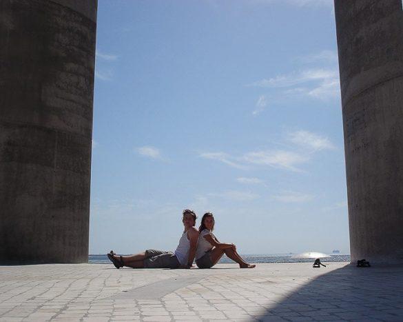 moški in ženska sedita na betonskih tleh naslonjena s hrbti