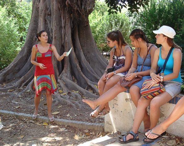 ženska v rdeči obleki ima govor pred skupino turistov, ki sedijo na betonski klopi
