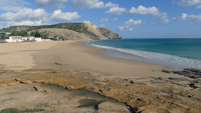 mivkasta plaža s klifi v ozadju. Luz, Portugalska
