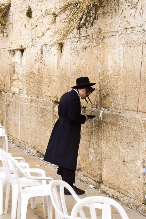 Jud v tradicionalni obleki se naslanja na zid žalovanja