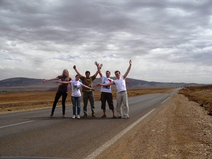 skupina popotnikov sredi ceste v puščavi, potovanje po maroku
