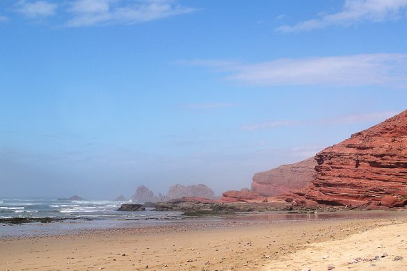 plaža Legiza, Maroko je peščena plaža z rdečimi skalnimi strukturami in naravnimi mostovi