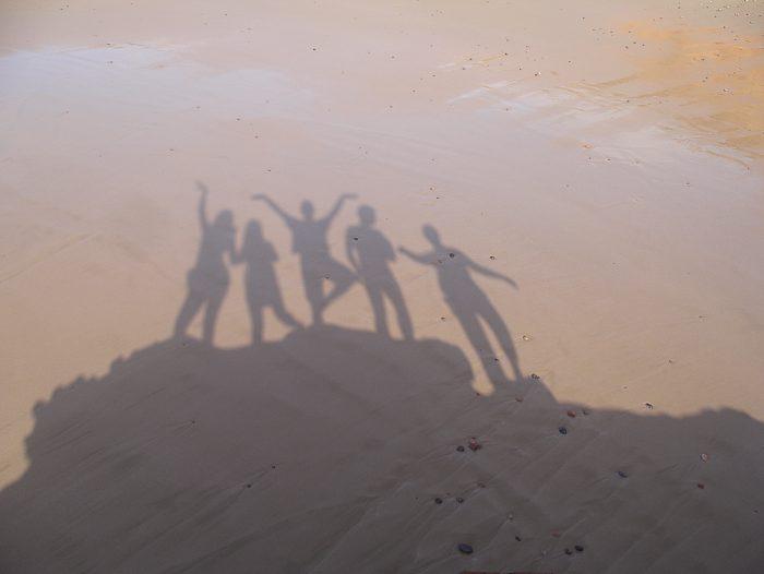 senca ljudi na peščeni plaži