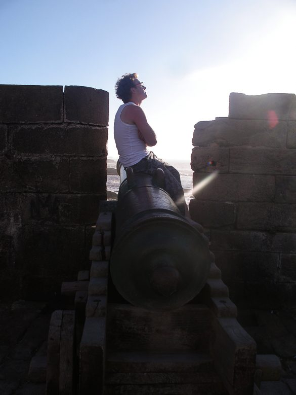 moški sedi na topu na srednjeveškem obzidju mesta Essaouira