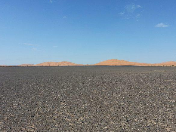 kamnita puščava s sipinami v ozadju