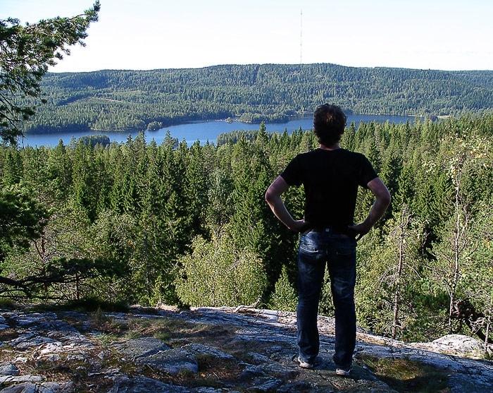 moški stoji na skali in občuduje razgled na park Koli, Finska