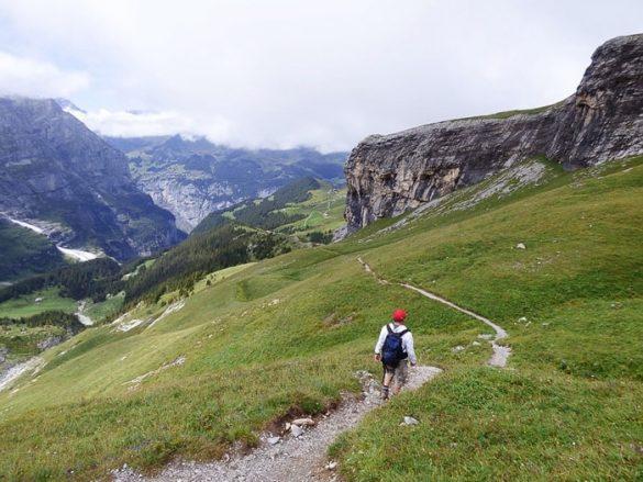 moški z rdečo kapo hodi po gorski poti nad dolino Lauterbrunnen