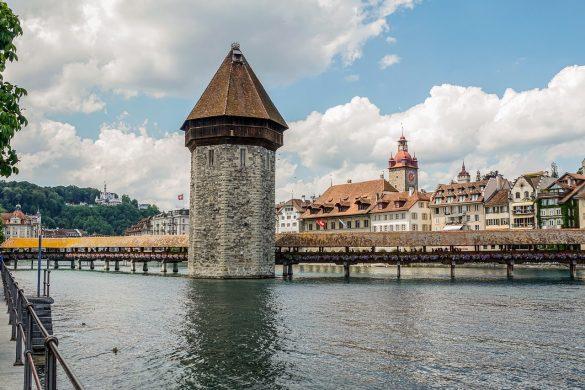kamnit vodni stolp sredi reki, ki povezuje dve strani lesenega mostu.