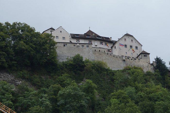 grad na vrhu zelene, z gozdom poraščene vzpeti. Grad Vaduz