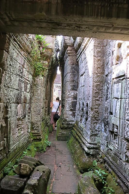 ženska v ozkem prehodu templja Ta Prohm