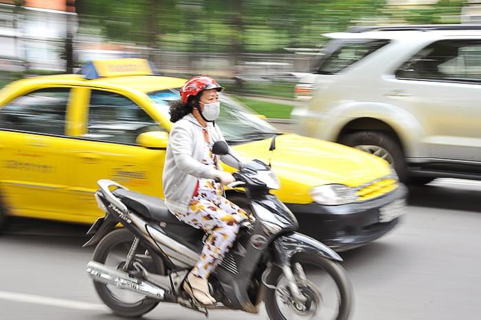 ženska na motorju z masko na obrazu