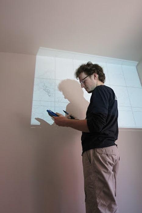 moški stoji pred projektorjem