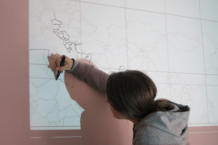ženska riše zemljevid sveta na steno