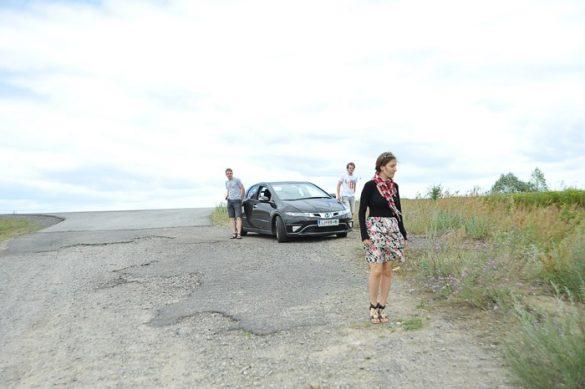 ženska v poletni obleki stoji ob zelo slabi cesti. V ozadju črn avto in dva moška