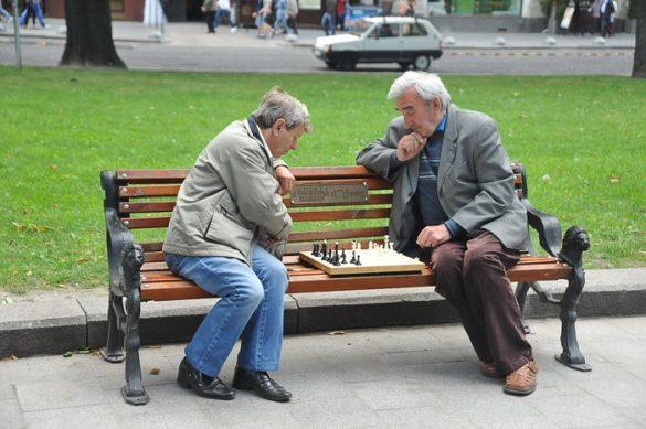 moška igrata šah na klopci na trgu v mestu Lvov