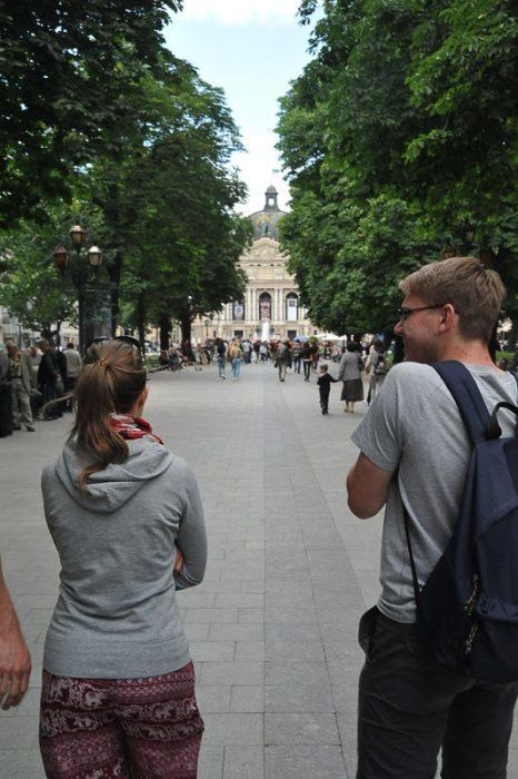 moški in ženska hodita proti operni hiši v Lvovu