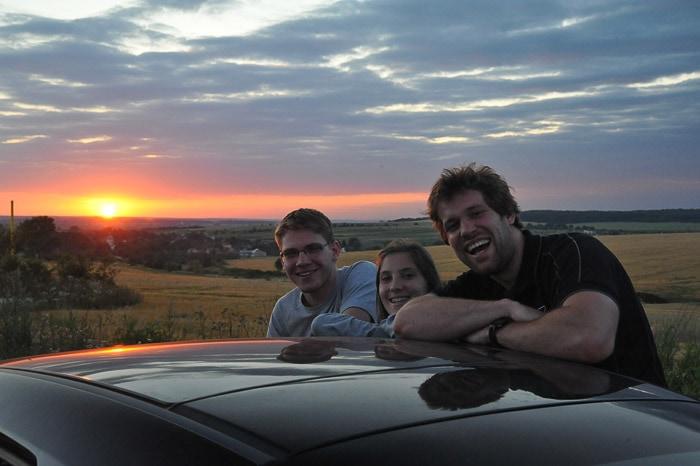 skupina mladih se naslanja na streho avtomobila in opazuje sončni zahod