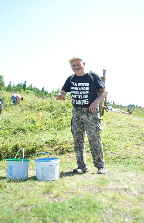 moški z nahrbtnikom in dvema vedroma nabira borovnice