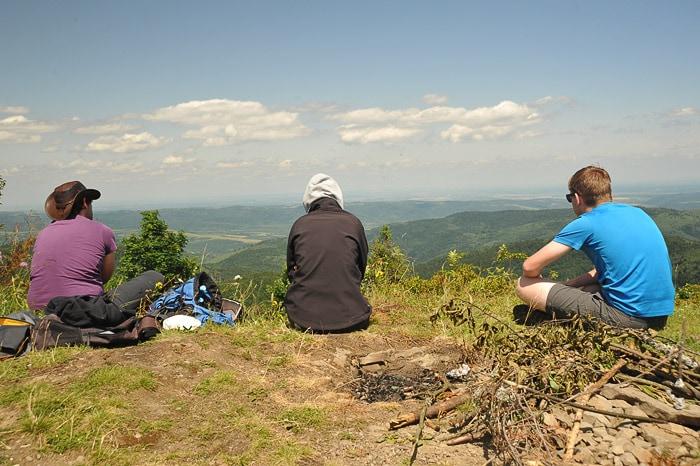 skupina mladih sedi na gorskem grebenu