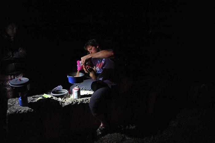 moški kuha večerjo na prenosnem gorilniku v soju čelne svetilke
