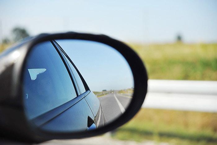pogled v vzvratno ogledalo na ravno cesto in rumena polja češke pokrajine