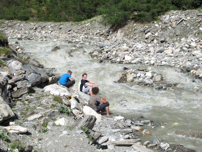 pohodniki si hladijo noge v potoku pod goro grossglocnker