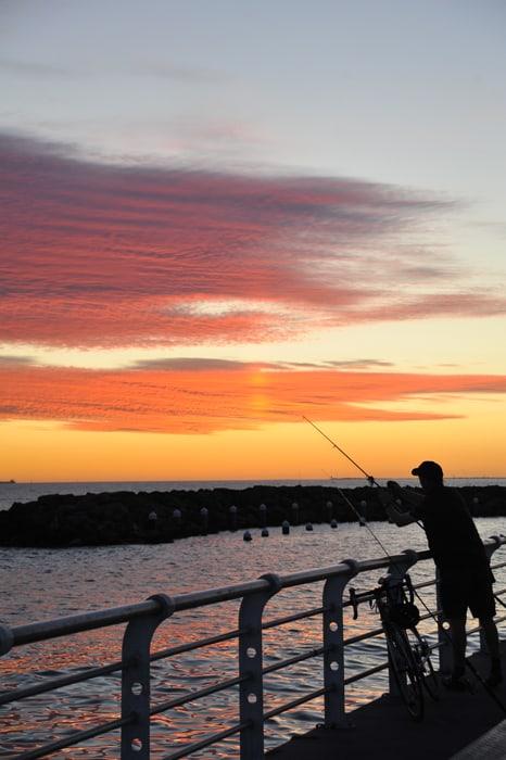 ribič ob sončnem zahodu Melbourne