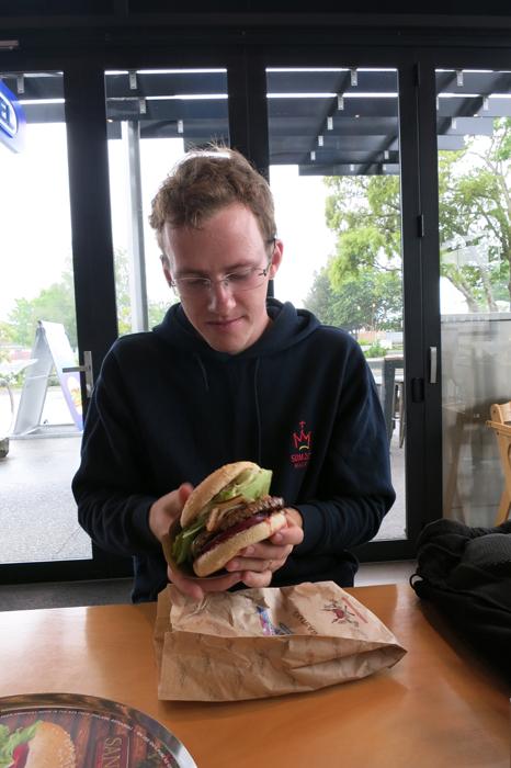 moški z burgerjem v roku. Burger Fuel, Nova Zelandija