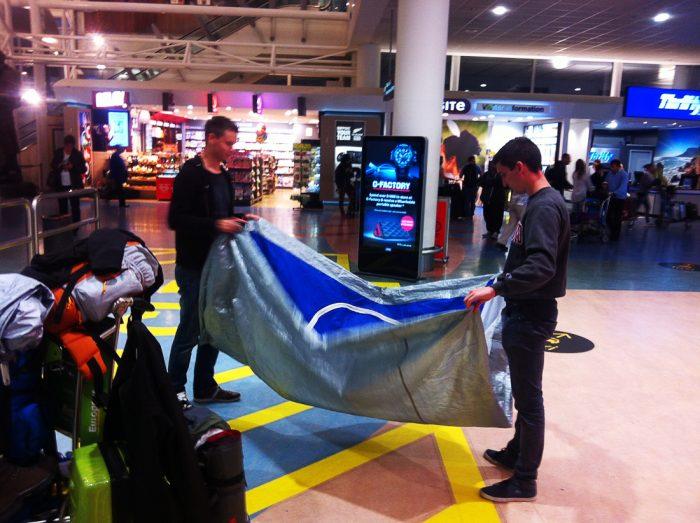 moška na letališču v Aucklandu zlagata šotor