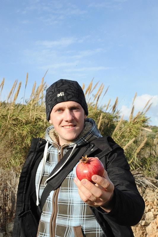 moški v roki drži granatno jabolko