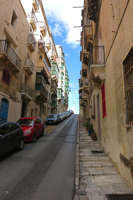 ozka ulica speljana v klanec. ob eni strani so parkirani avtomobili, na obeh straneh se dvigujejo visoke starinske hiše