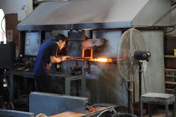 moški vzema žareče steklo iz peči