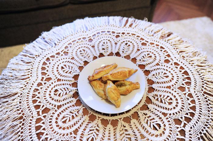 pečeni žepki - pastizzi na belem krožniku, ki stoji na okrogli mizi z lepim čipkastim prtom