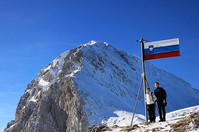 moški in ženska ob slovenski zastavi, v ozadju Brana. Kamniško sedlo