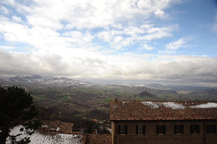 pogled na zasnežene strehe hiš in v daljavi zasnežene gore
