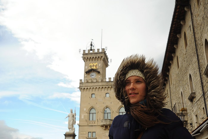 ženska s kapuco na glavi stoji pred italijansko palačo