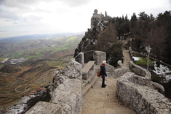 ženska hodi po tlakovani poti proti gradu